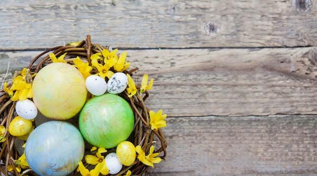 Nest mit farbigen eiern mit blumen auf holzbeschaffenheit.