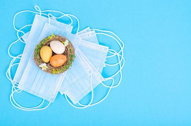 Nest mit hell gefärbten eiern mit medizinischen masken. ostern in der covid-19-pandemie