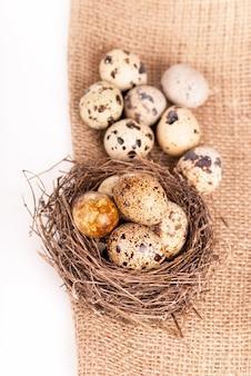 Nest mit wachteleiern auf einer leinwand auf einem weißen hintergrund