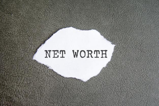 Net worth-zeichen auf dem zerrissenen papier auf dem grauen hintergrund