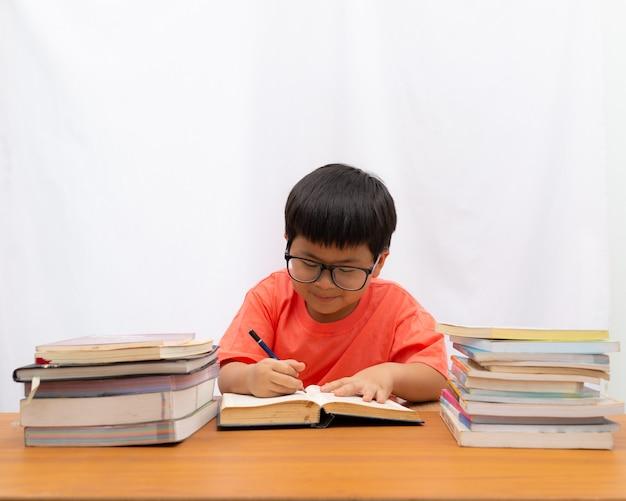 Nett ein kleiner junge, der auf dem tisch ein buch mit auf weißem hintergrund schreibt,