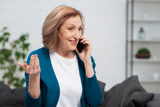 Nette ältere frau, die am telefon spricht