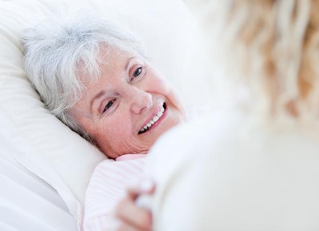 Nette ältere frau, die auf einem krankenhausbett spricht mit ihrer enkelin liegt