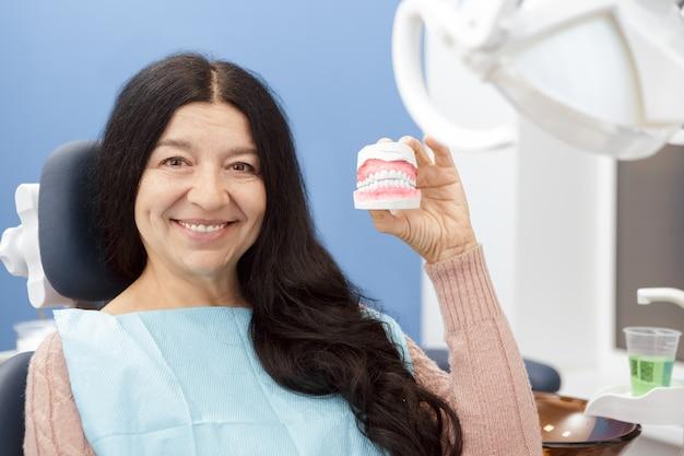 Nette ältere frau, die zahnform im zahnarztbüro halten lächelt
