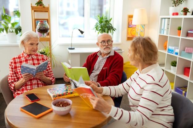 Nette ältere leute, die über verschiedene bücher sprechen, während sie am tisch sitzen