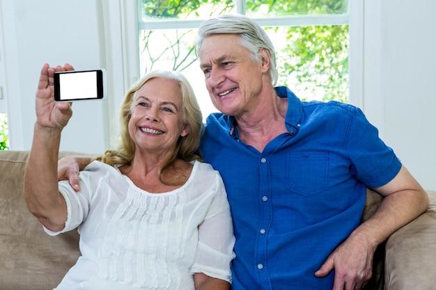 Nette ältere paare, die zu hause selfie nehmen