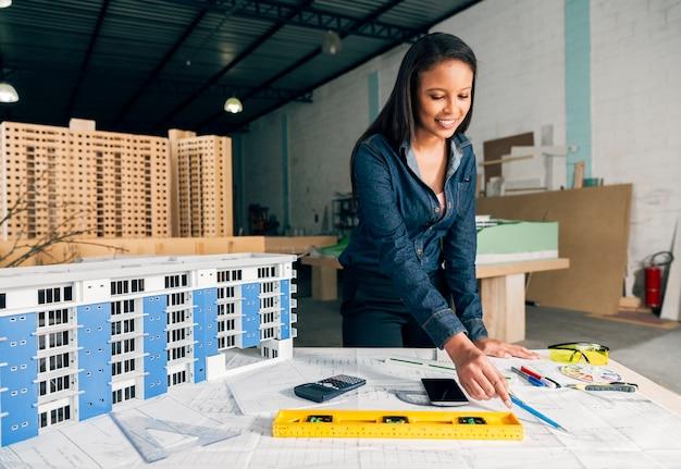 Nette afro-amerikanische dame, die nahes modell des gebäudes auf tabelle steht
