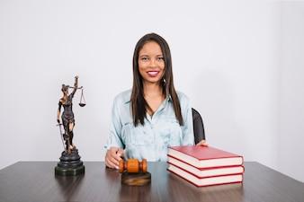 Nette Afroamerikanerfrau bei Tisch mit Hammer, Büchern und Statue