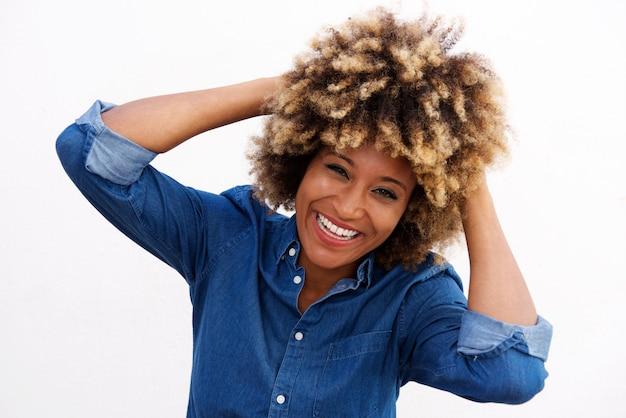 Nette afroamerikanerfrau, die mit den händen im haar lacht