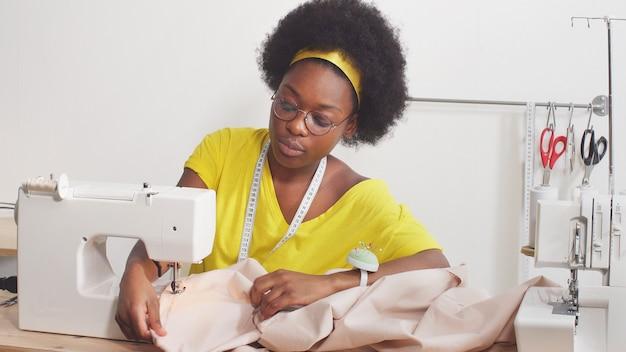 Nette afroamerikanische frau, die eine nähmaschine benutzt, näht kleidung