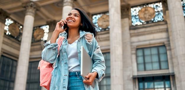 Nette afroamerikanische studentin, die am telefon mit einem rucksack und einem laptop nahe dem campus spricht.