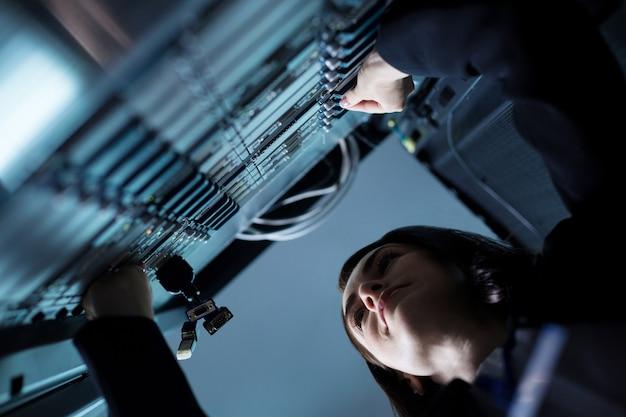 Nette angenehm entzückte frau, die in der nähe des netzwerkservers steht und die usb-kabel während ihrer arbeit überprüft