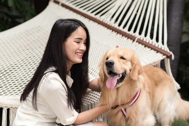 Nette asiatin, die zu hause mit ihrem hund des goldenen apportierhunds im garten spielt
