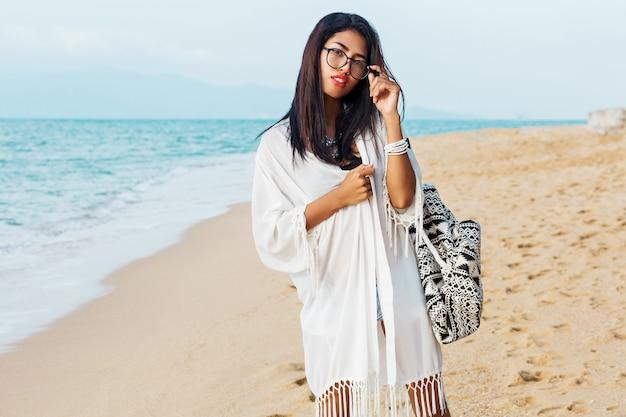 Nette asiatische frau des reisenden im weißen kleid, das auf dem tropischen strand geht. hübsche frau, die urlaub genießt. schmuck, armband und halskette.