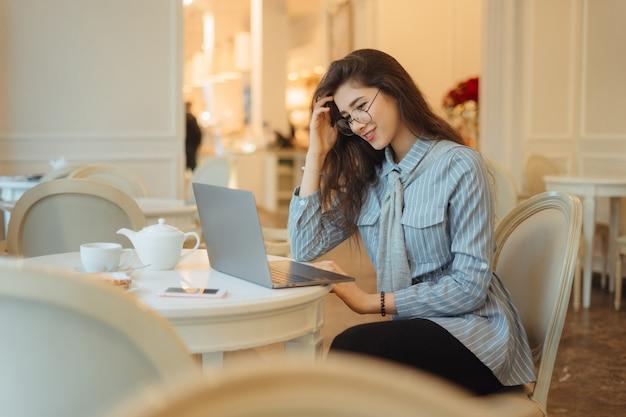 Nette asiatische frau, die eine tasse tee beim verwenden des laptop-computers im café hat