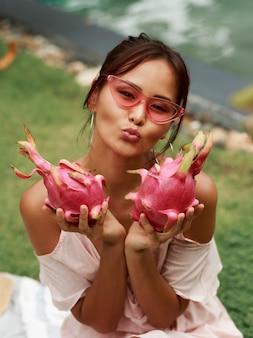 Nette asiatische frau, die rosa drachenfrüchte in den händen hält