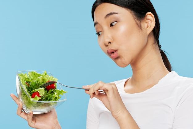 Nette asiatische frau, die salat, diätkonzept isst