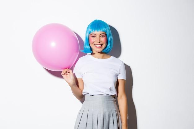 Nette asiatische frau im blauen perücken- und schulmädchenkostüm für halloween, das rosa ballon hält und lächelt, stehend.