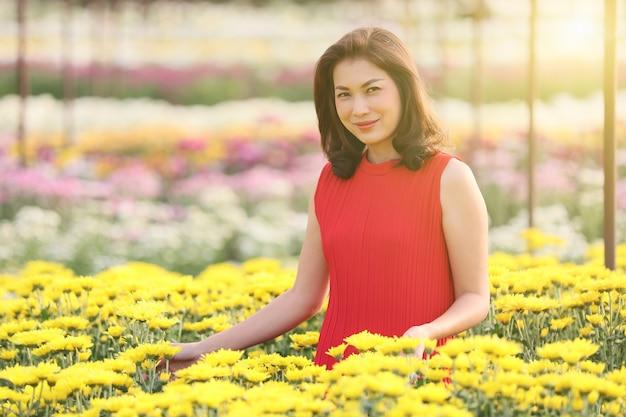 Nette asiatische frau im roten kleid, die im blumengarten mit vielen arten und bunten blumen steht. schönes sonnenlicht im hintergrund.