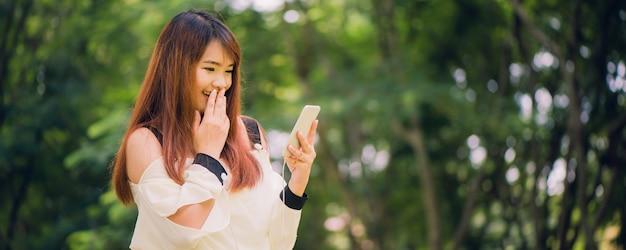 Nette asiatische frau liest angenehme textnachricht auf handy beim sitzen im park im warmen frühlingstag, herrliche frau, die musik in den kopfhörern hört. panorama-banner.