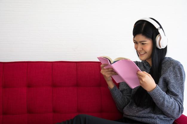 Nette asiatische frau sitzt auf dem sofa am morgen und liest ein buch