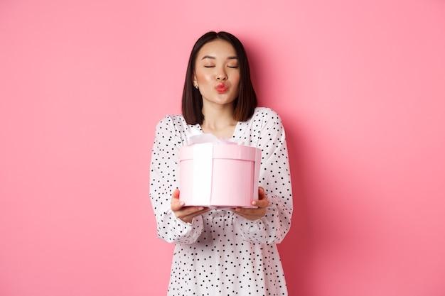 Nette asiatische freundin gratulieren mit valentinstag und geben niedliches romantisches geschenk in der schachtel, fältchenlippen für kuss, stehend über rosa hintergrund