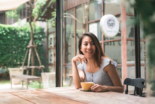 Nette asiatische junge frau, die den warmen kaffee oder tee beim sitzen genießen im café trinkt