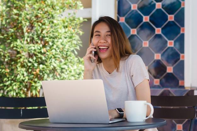 Nette asiatische junge frau, die in trinkendem kaffee des cafés sitzt und smartphone für die unterhaltung verwendet