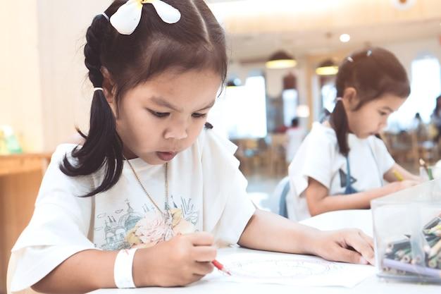 Nette asiatische kindermädchenmalerei und -zeichnung mit zeichenstift mit spaß