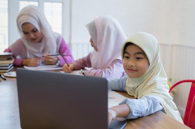 Nette asiatische moslemische mädchen, die hausaufgaben im klassenzimmer erledigen.