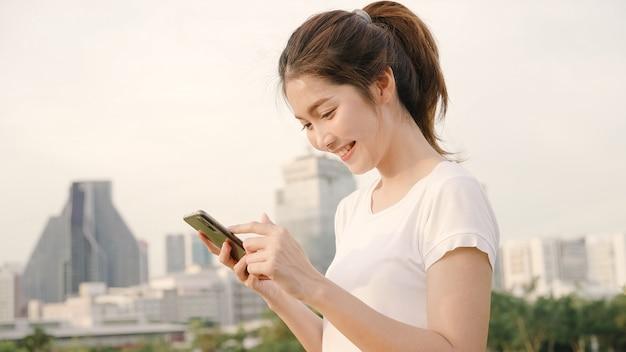 Nette asiatische touristische bloggerfrau, die smartphone für richtung verwendet und auf standortkarte beim reisen auf die straße in die im stadtzentrum gelegene stadt schaut.
