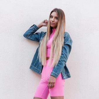Nette attraktive junge frau blondine mit langen haaren in vintage rosa shorts in einem stilvollen rosa top in einer blauen jeansjacke steht auf der straße in der nähe einer vintage wand an einem sommertag. sinnliches modisches mädchen