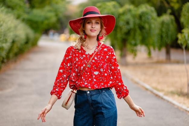 Nette attraktive stilvolle blonde lächelnde frau in strohrotem hut und bluse sommermode-outfit