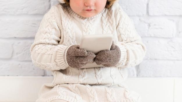 Nette babyhände, die eine tablette halten