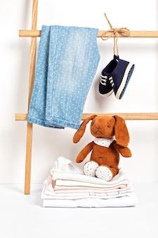 Nette babykleidung, die auf dem gestell mit schuhen und spielzeugen hängt