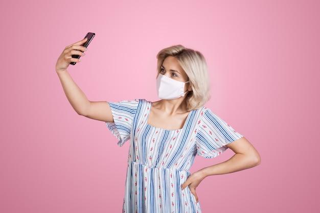 Nette blonde dame in einem sommerkleid und einer medizinischen maske auf gesicht macht ein selfie auf einer rosa wand