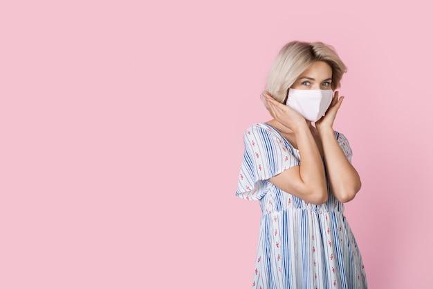 Nette blonde dame mit medizinischer maske auf gesicht und sommerkleid, das beiseite auf einer rosa wand mit freiem raum aufwirft