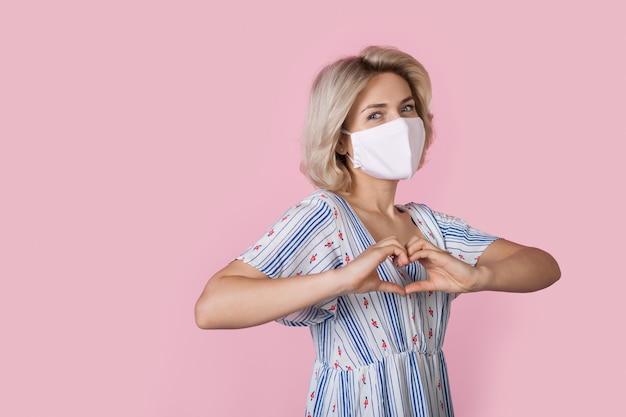 Nette blonde frau, die eine medizinische maske und ein kleid trägt, gestikuliert herzzeichen auf einer rosa wand