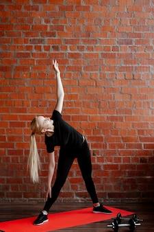 Nette blonde frau, die fitness auf dem hintergrund einer backsteinmauer des hauses während der quarantäne tut.