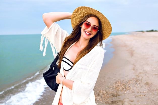 Nette blonde frau, die selfie am ozeanstrand macht, boho-outfit und lustige sonnenbrille tragend, vintage strohhut, kuss senden.