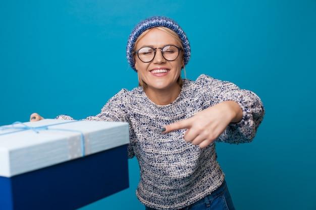 Nette blonde frau hält ein geschenk und zeigt auf ihn, während sie einen hut und einen warmen pullover an einer blauen studiowand trägt