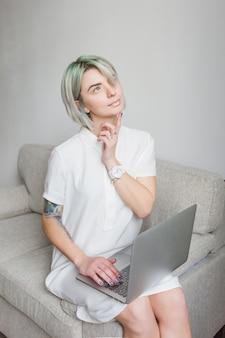 Nette blonde frau mit kurzer frisur sitzt auf sofa