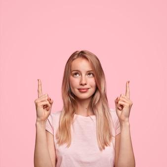Nette blonde frau mit langen haaren, zeigt mit zwei vorderfingern nach oben