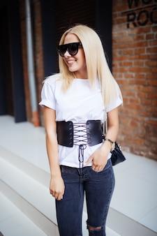 Nette blonde junge frau nahe ziegelmauer und lächeln