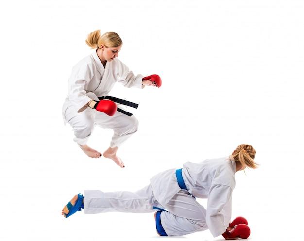Nette blonde mädchen, die karate auf weiß trainieren