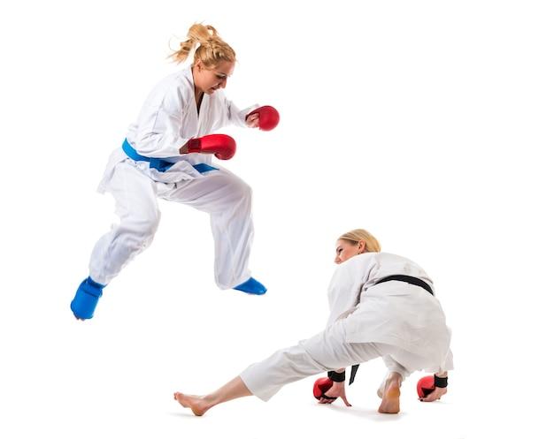 Nette blonde mädchen karate sind in der ausbildung in einem kimono auf einem weißen hintergrund beschäftigt.