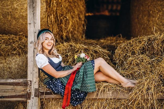 Nette blondine im dirndl, traditionelles festkleid mit blumenstrauß der feldblumen, die auf dem hölzernen zaun am bauernhof sitzen