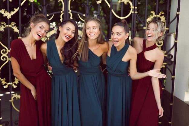 Nette brautjungfern in den erstaunlichen roten und grünen kleidern, die nahe den toren, partei, hochzeit, spaß, frisur, jung, lustig, make-up, ereignis, lächelnd, lachend aufwerfen