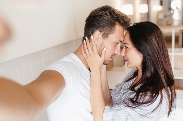 Nette brünette dame mit weißer maniküre, die ehemanns gesicht hält, während er selfie macht