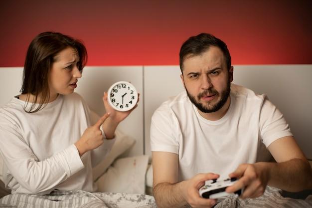 Nette brünette frau im bett zeigt auf wache, während ihr bärtiger freund videospiele spielt und nicht auf sie achtet